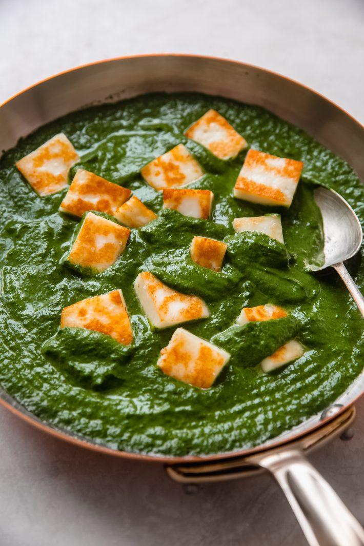 palak paneer in frying pan with spoon
