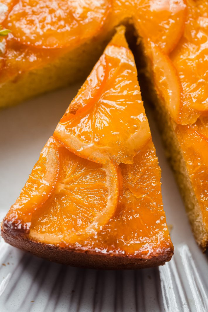 slice of whole orange cake with candied oranges on top