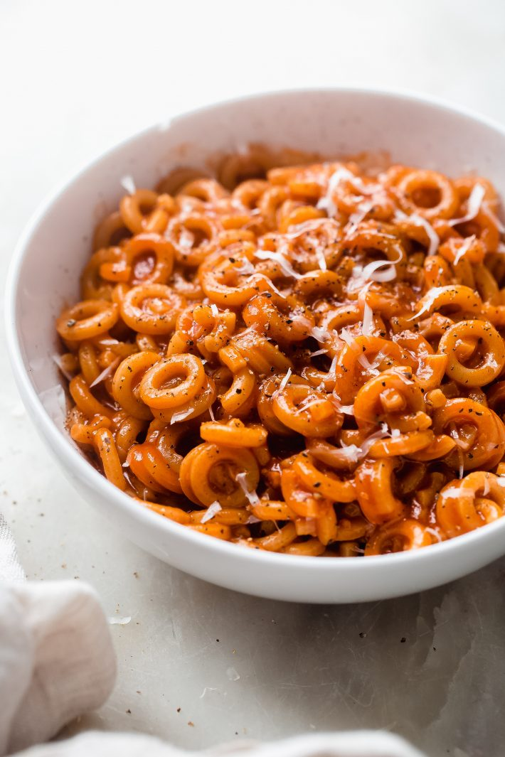 homemade spaghettiOs topped with shaved pecorino Romano cheese and black pepper