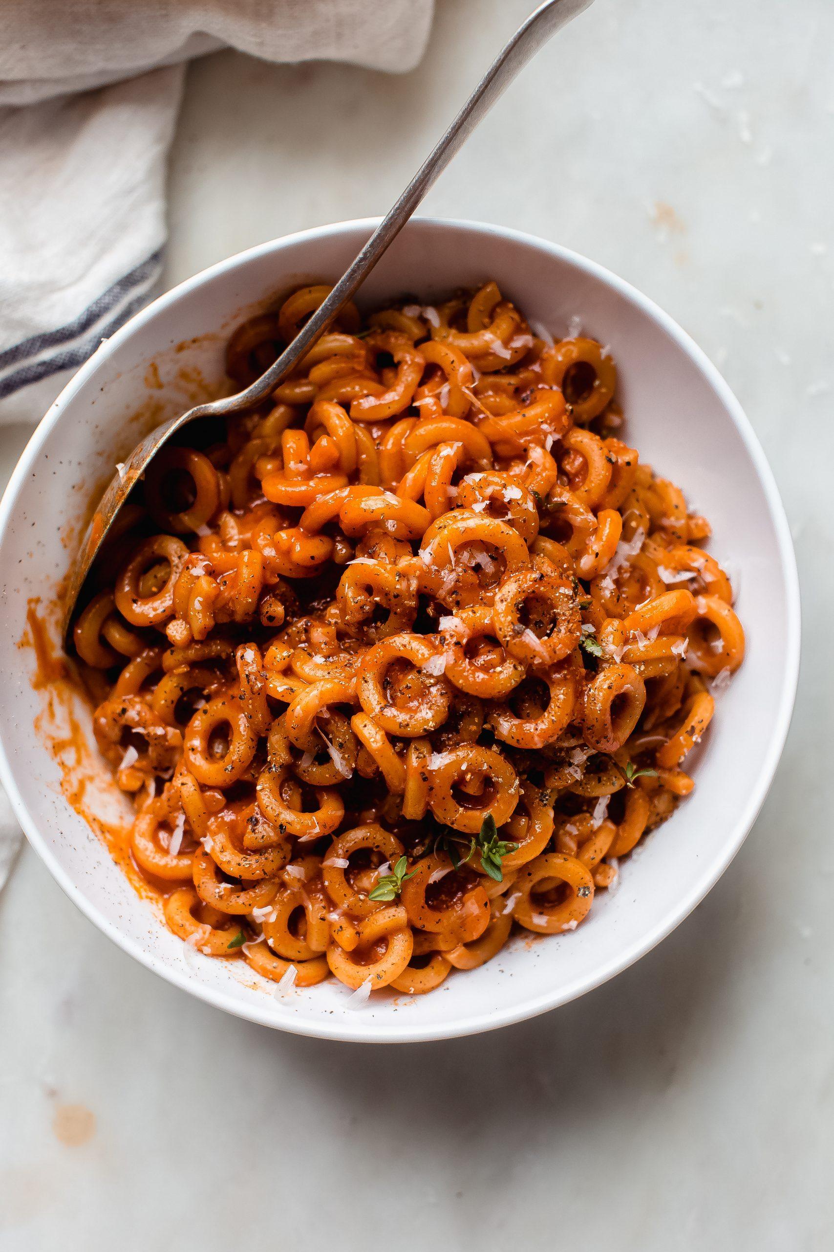 bowl of spaghettiOs on white marble