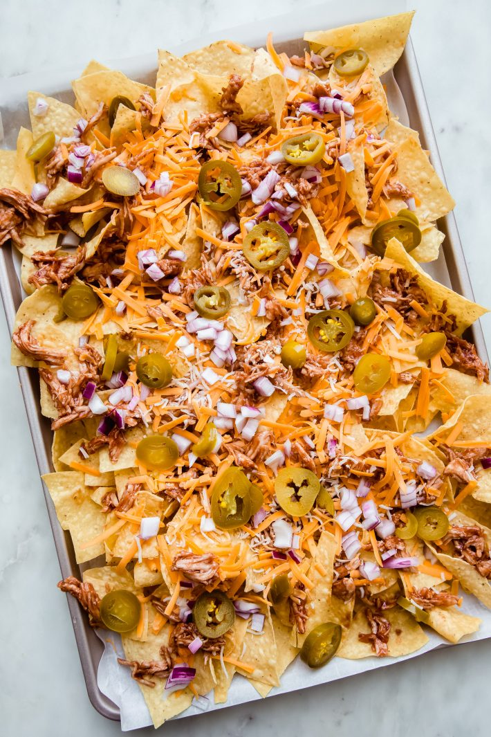 tortilla chips on sheet pan layered with toppings