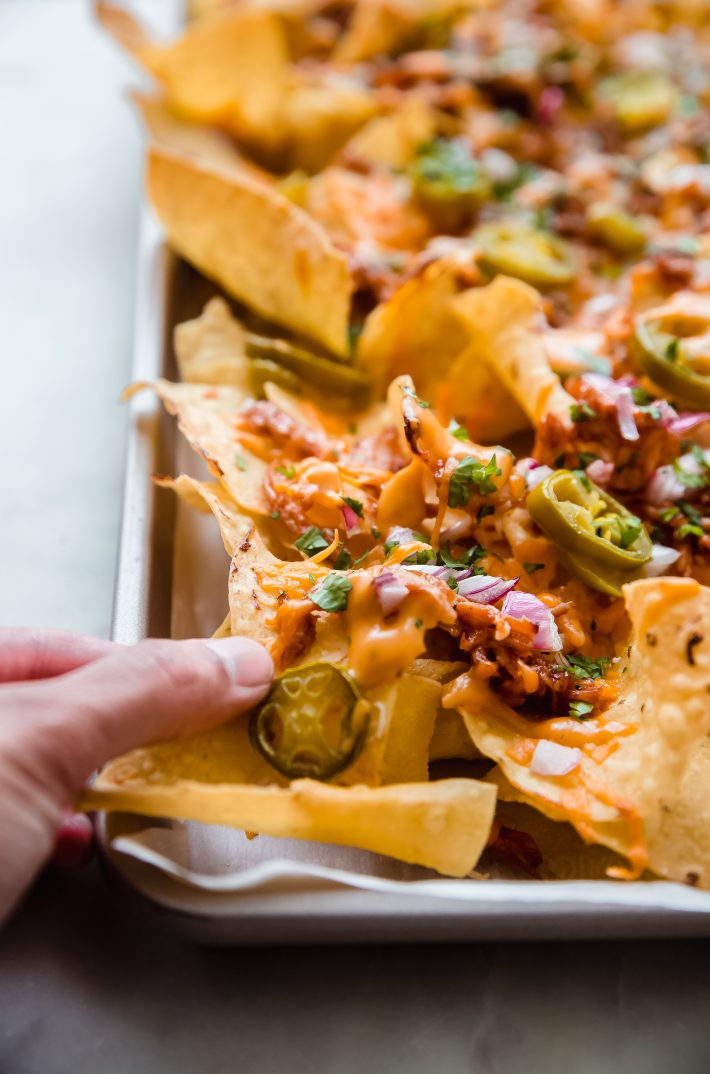 hand holding nachos with toppings on sheet pan