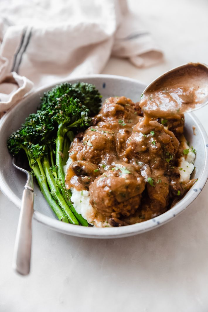 bowl of mashed potatoes and sautéed broccolini topped with Salisbury steak meatballs