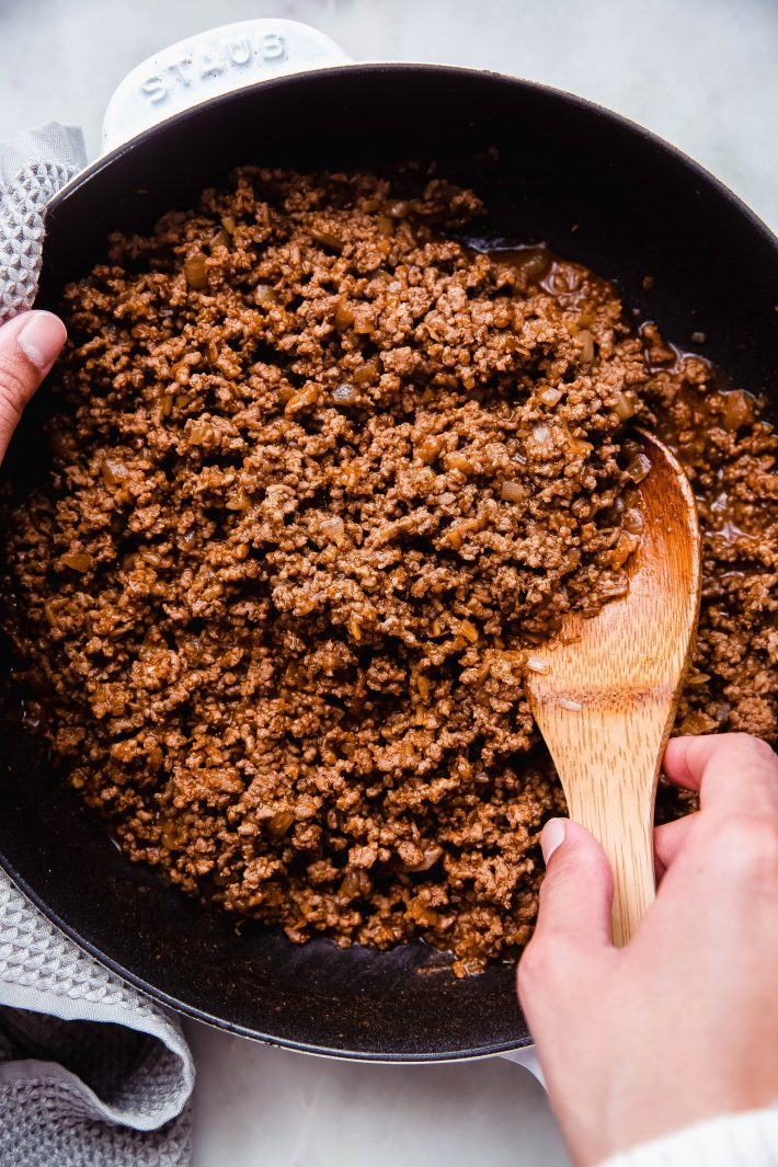 cooked taco meat in white cast-iron skillet with wooden spoon