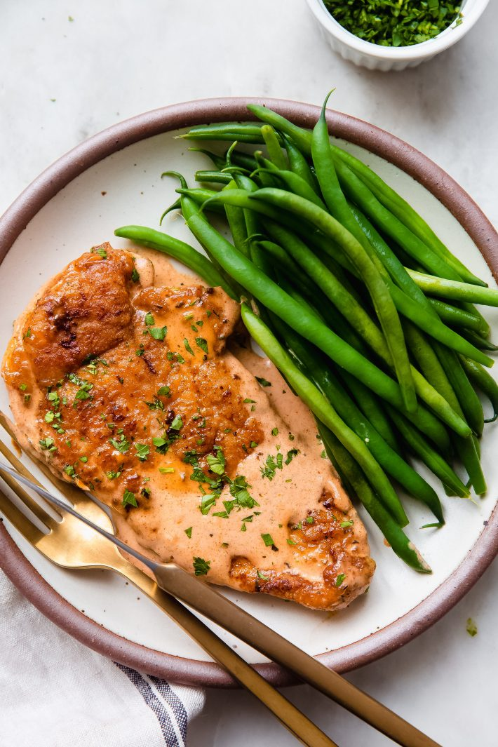 chicken with sauce and steamed green beans on plate