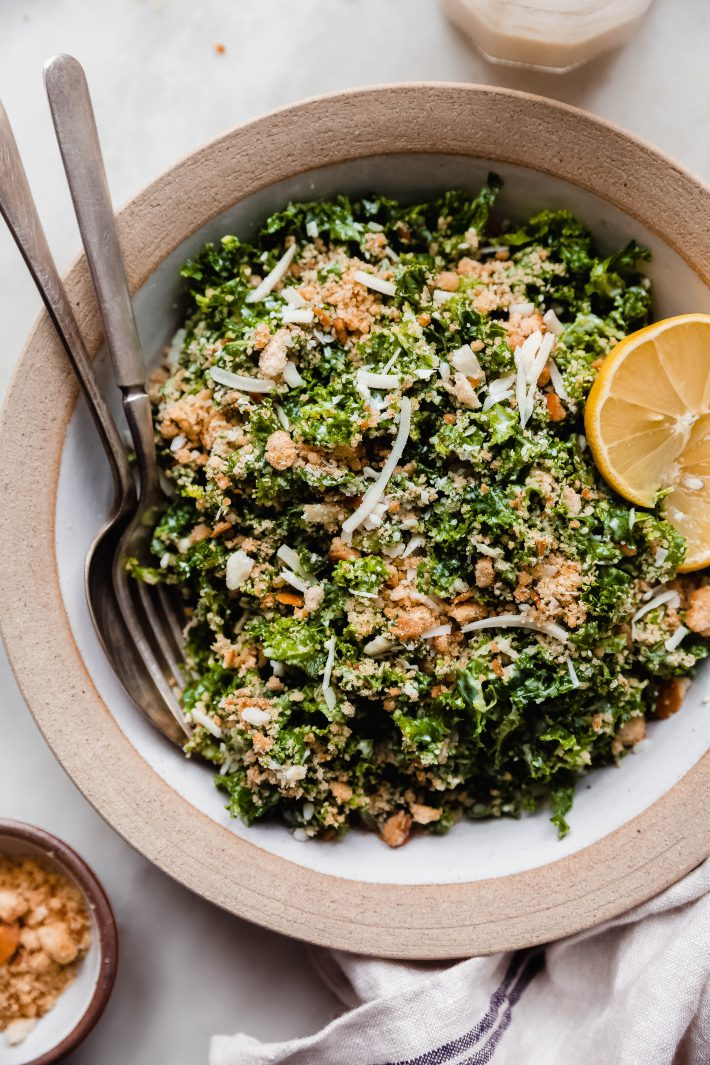 rimmed deep bowl with shredded kale Caesar salad topped with toasted parmesan bread crumbs