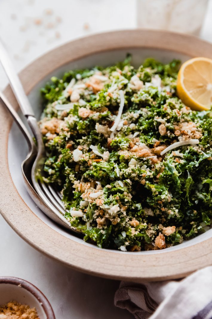 spoon and fork resting in salad bowl showing crunchy bread topping on kale