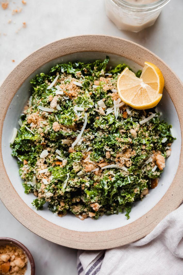 kale salad in bowl with two lemon wedges