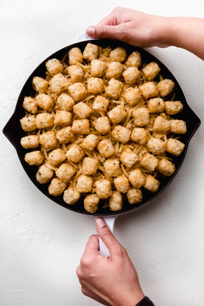 skillet with cottage pie filling topped with frozen potato puffs
