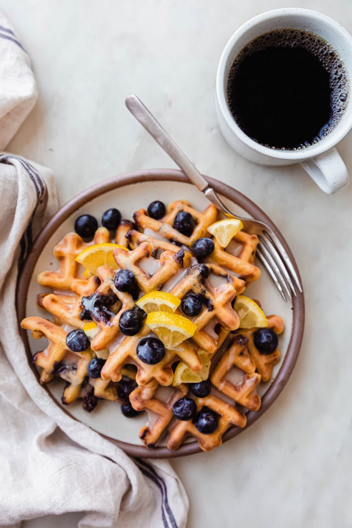 plateful of waffles with lemon wedges and blueberries on white marble with fork and coffee
