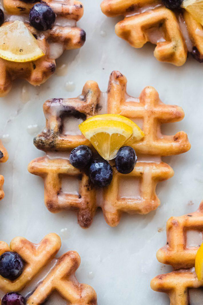 single glazed lemon blueberry waffle on white marble topped with lemon wedge and blueberries