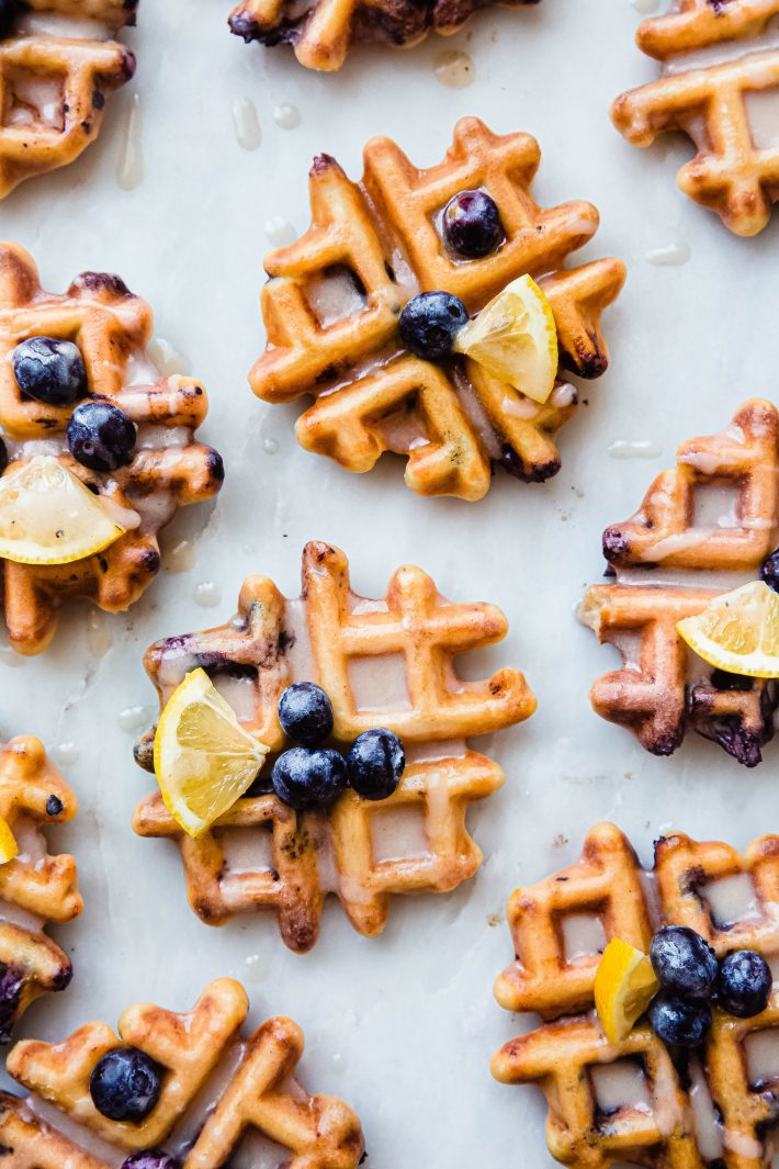 marble board with prepared glazed waffles topped with lemon wedges and fresh blueberries
