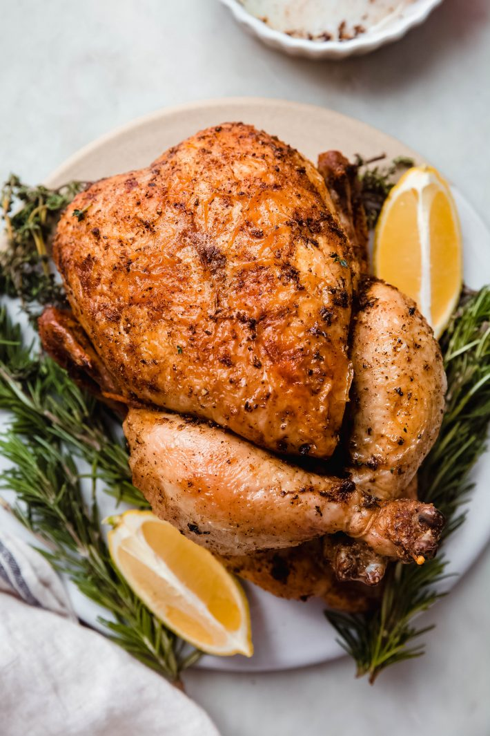 prepared roasted chicken surrounded by herbs and lemon wedges