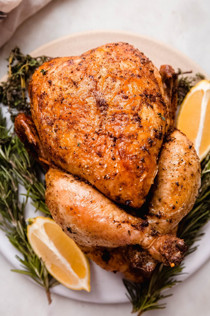 close up of oven rotisserie chicken on board with rosemary and lemon wedges