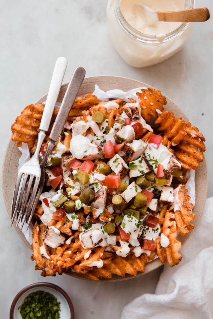 prepared fries topped with chicken shawarma and toppings with forks on white marble