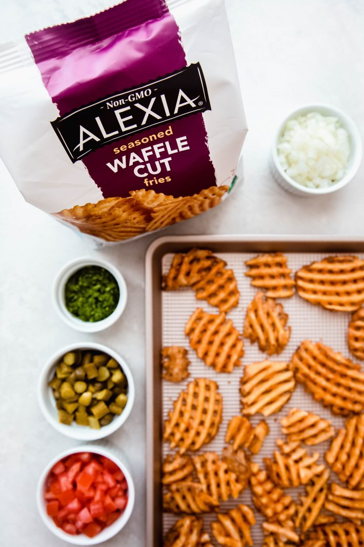 bag of Alexia waffle cut fries with fries on sheet pan and toppings on white marble
