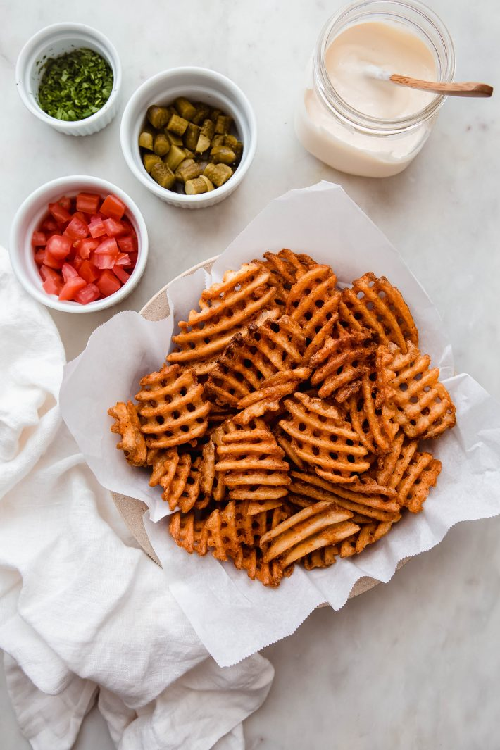 baked waffle fries on parchment with toppings surrounding