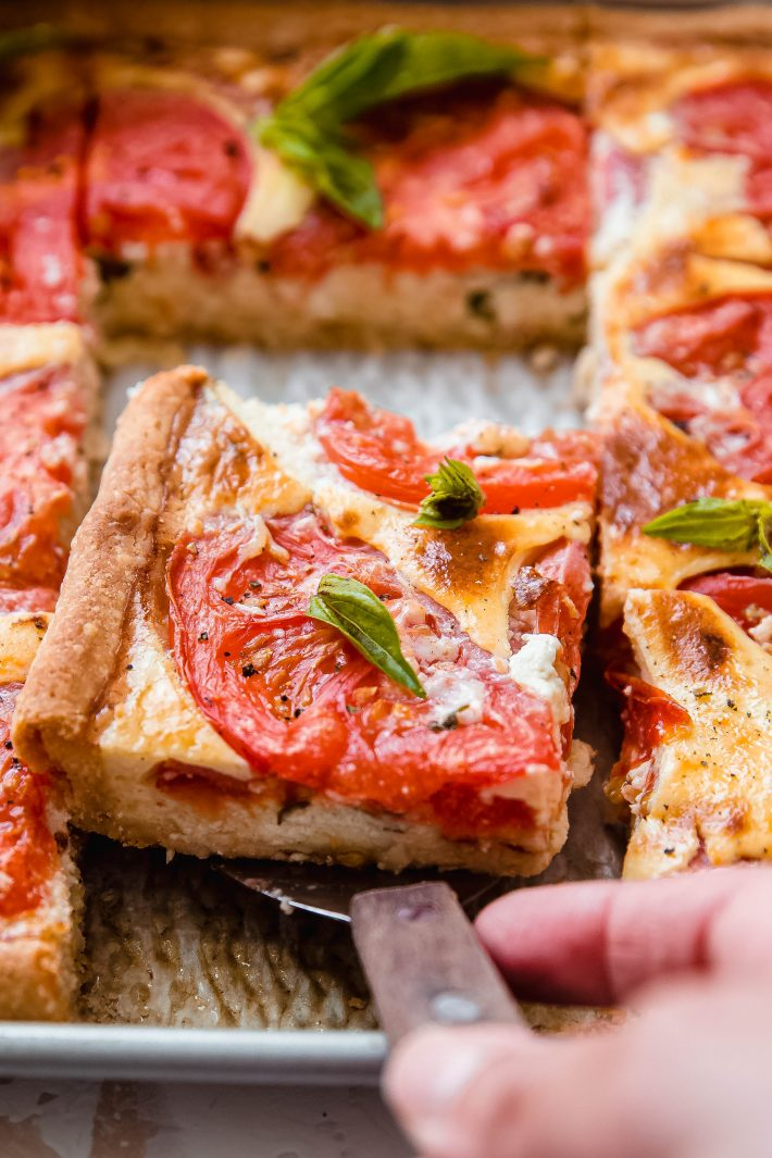 portioned sheet pan tomato quiche on spatula lifting from pan