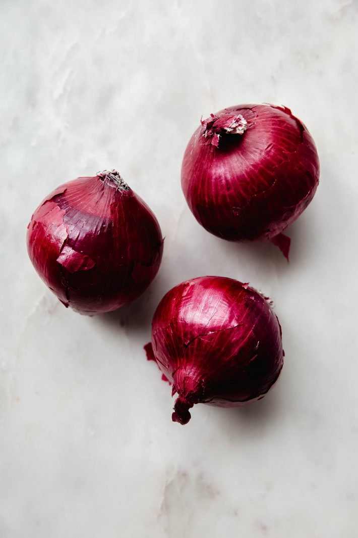 three red onions on white marble