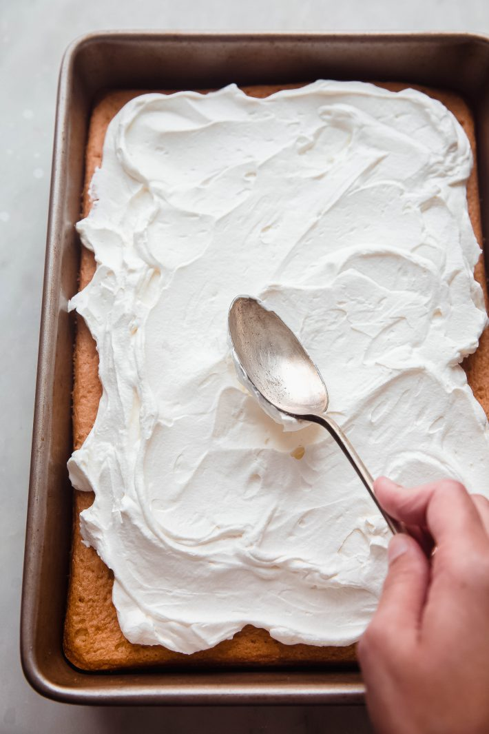 hand spreading whipped cream on cake with spoon