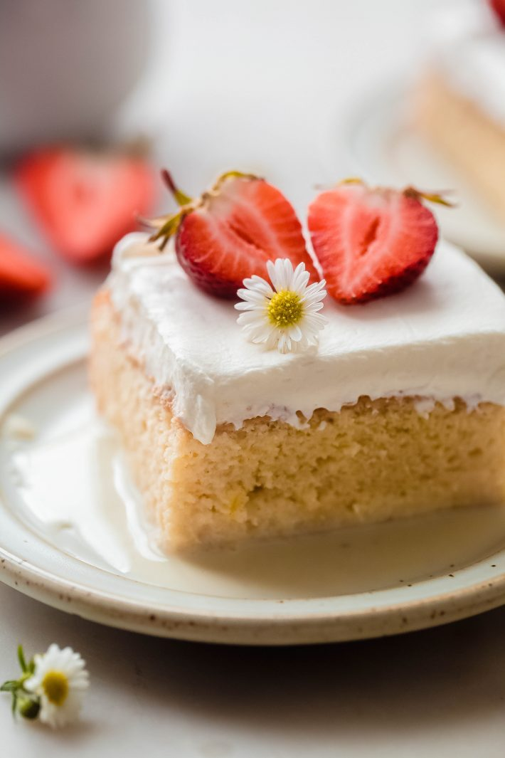 slice of tres leches cake on plate with milk syrup, whipped cream, strawberries, and a small flower