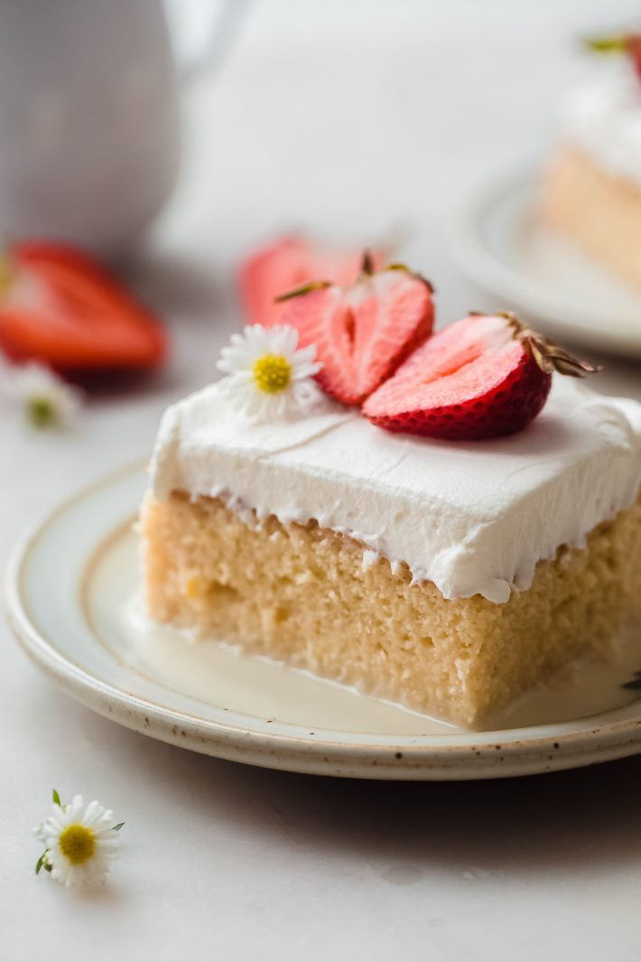 soaked milk cake with whipped cream and strawberries on plate with extra milk