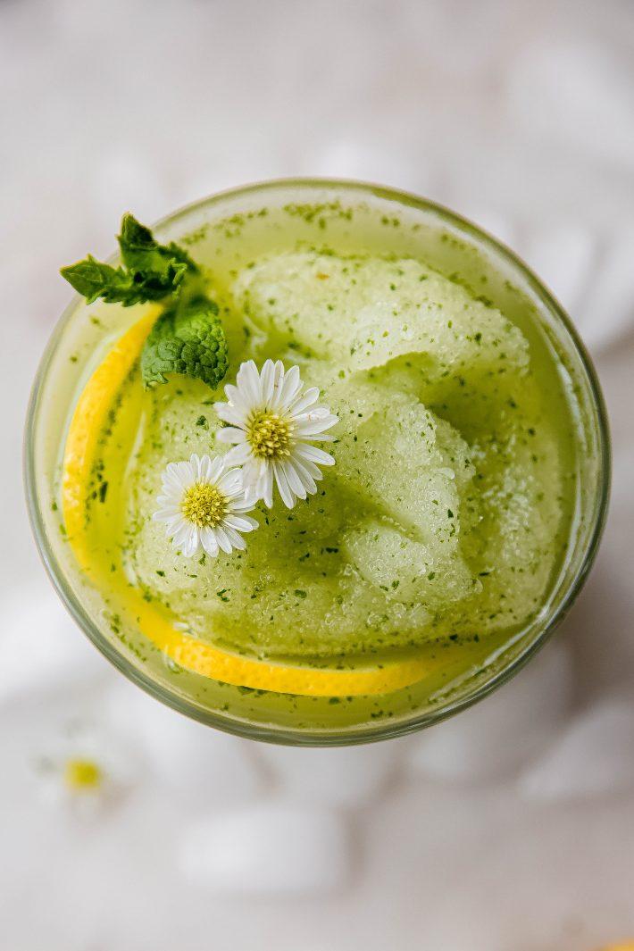 blended mint lemonade slushie in glass on white marble