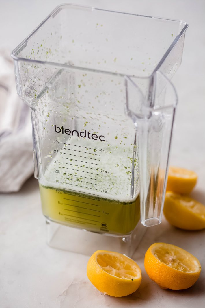 blender with blended lemon juice, lime juice, mint, sugar, and water on white marble