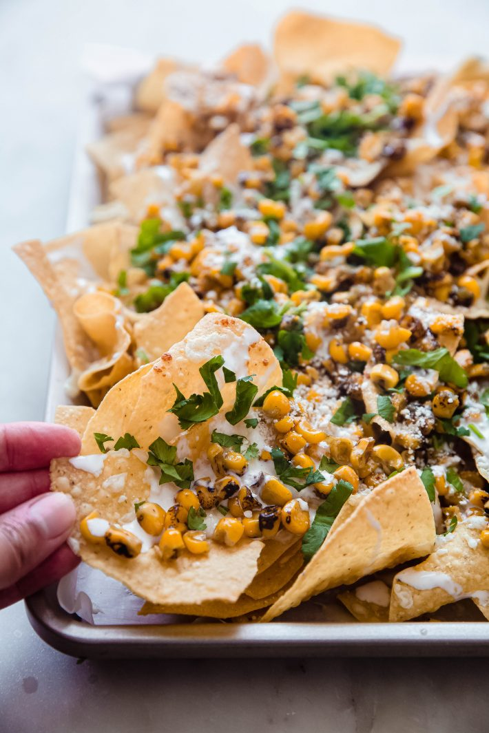 tortilla chips topped with butter fire-roasted corn, creamy and cilantro on sheet pan