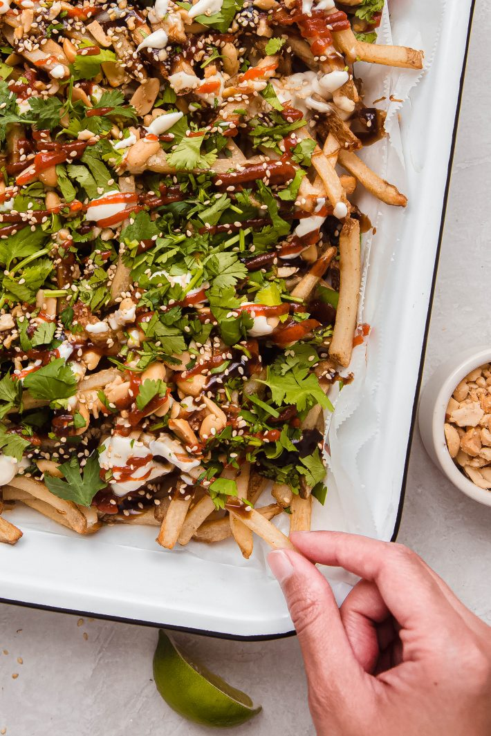 hand grabbing loaded fries from enameled dish