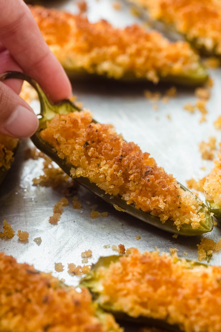 hand holding baked jalapeno popper on sheet pan