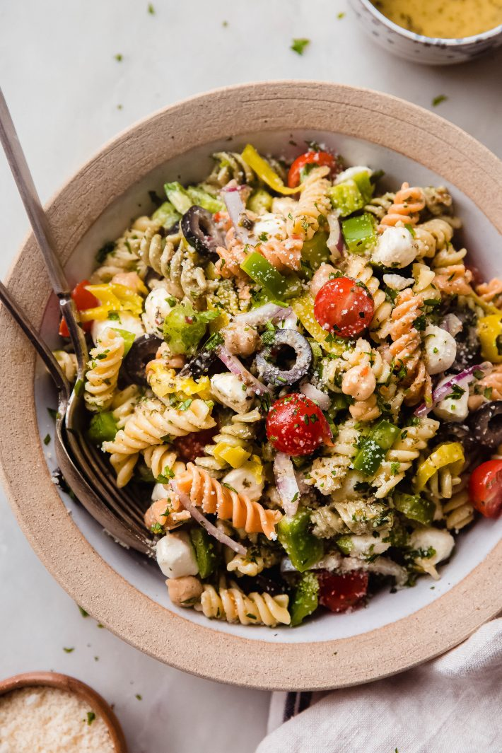 italian pasta salad in rimmed bowl on white marble