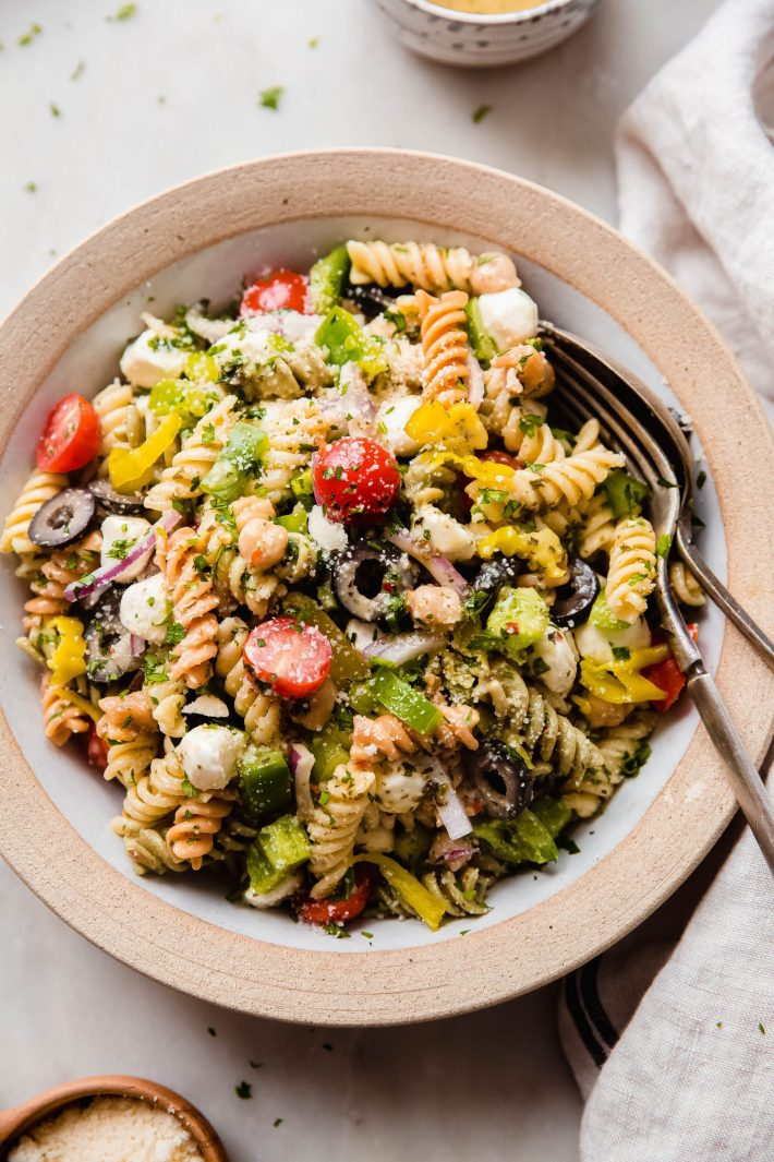 pasta salad in rimmed plate on white marble