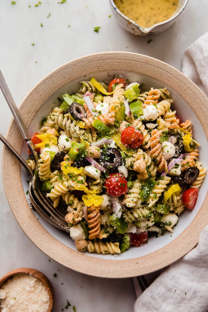 italian pasta salad in rimmed plate with fork and spoon on white marble