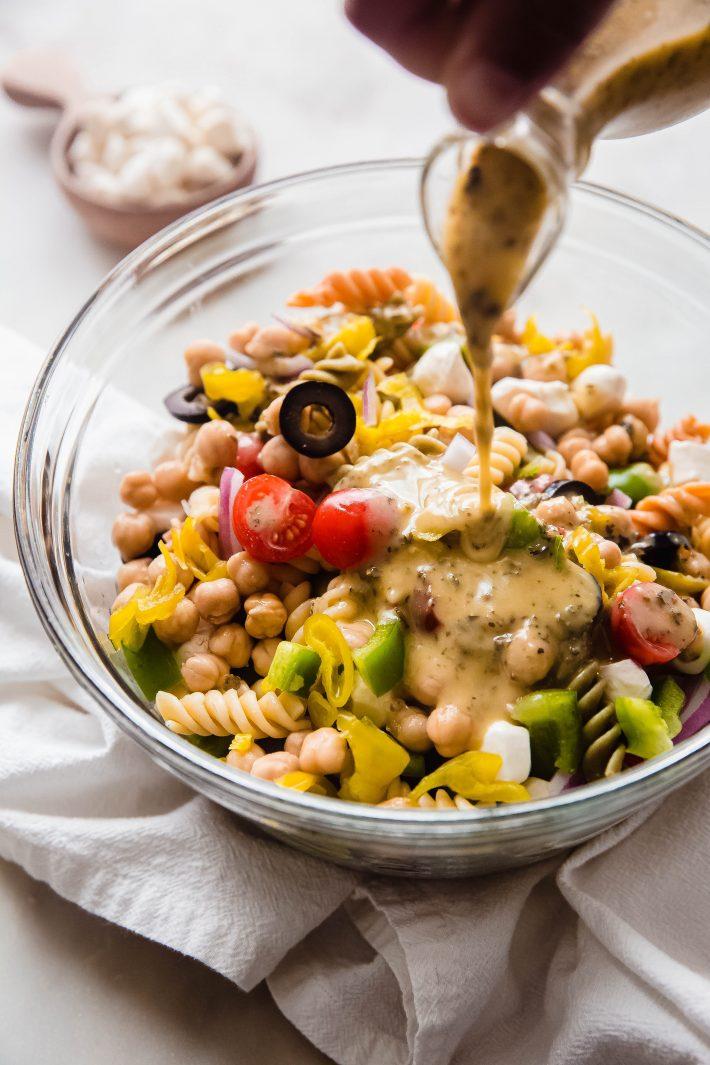 pouring dressing on pasta salad ingredients