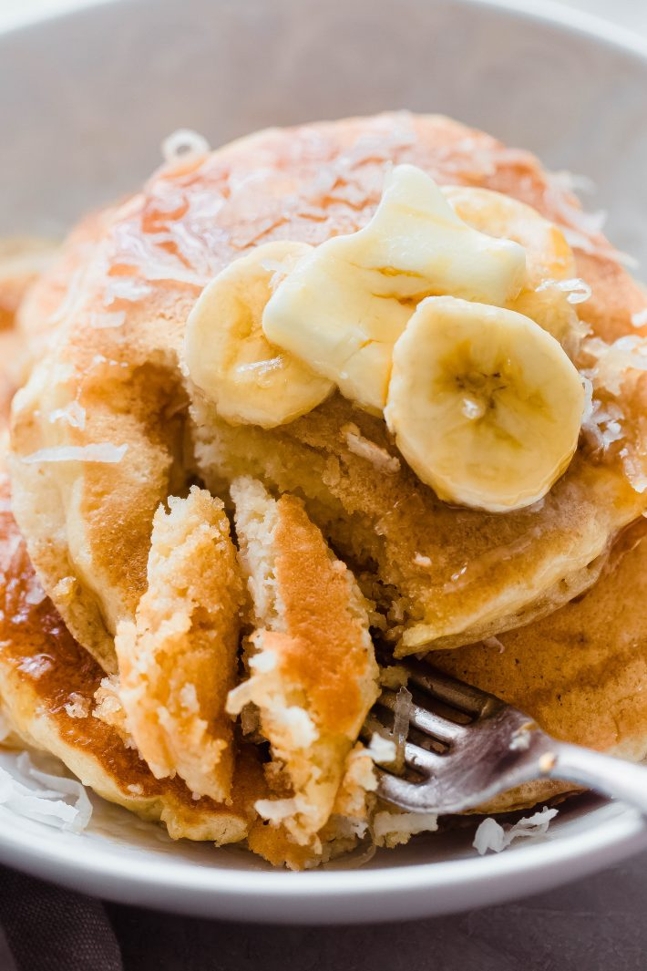 plate with pancakes topped with banana slice sand butter pat