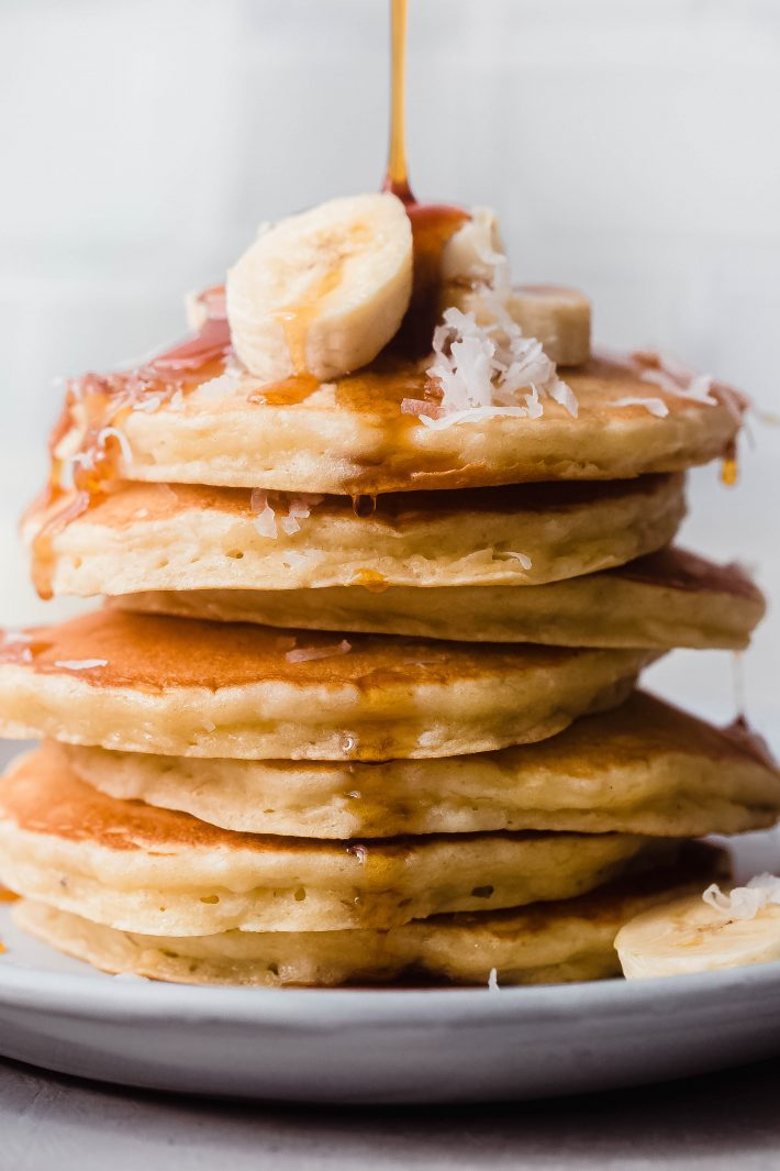 syrup pouring over pancakes with banana slices and shredded coconut