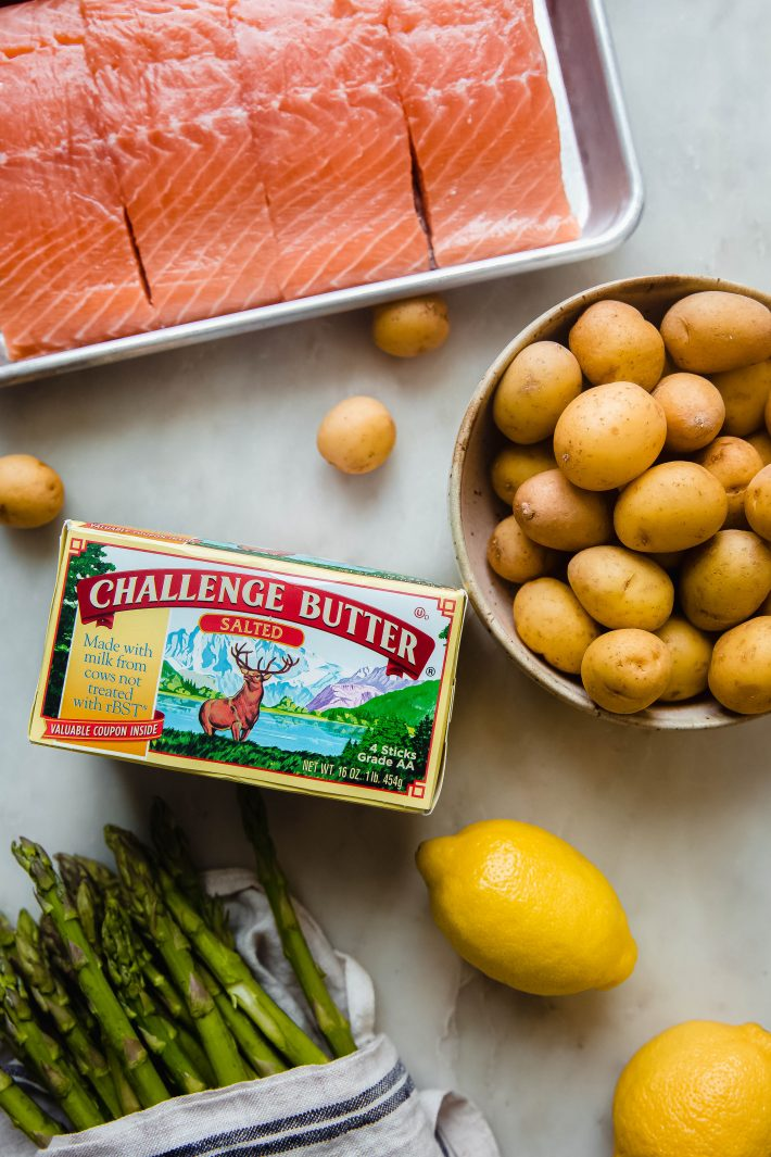 salmon, potatoes, asparagus, lemons' and challenge butter on white marble