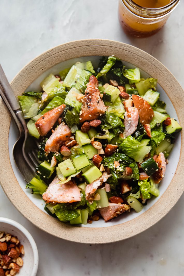 sesame ginger salmon salad in rimmed bowl with spoon and fork