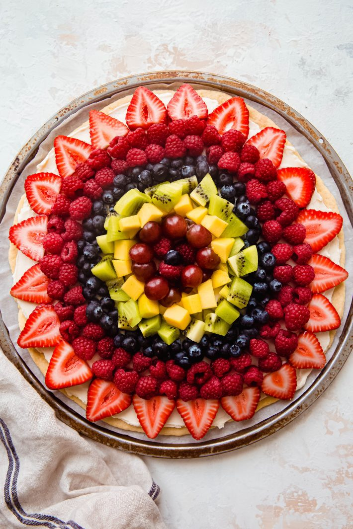 fruit pizza topped with cream cheese icing and fresh fruit