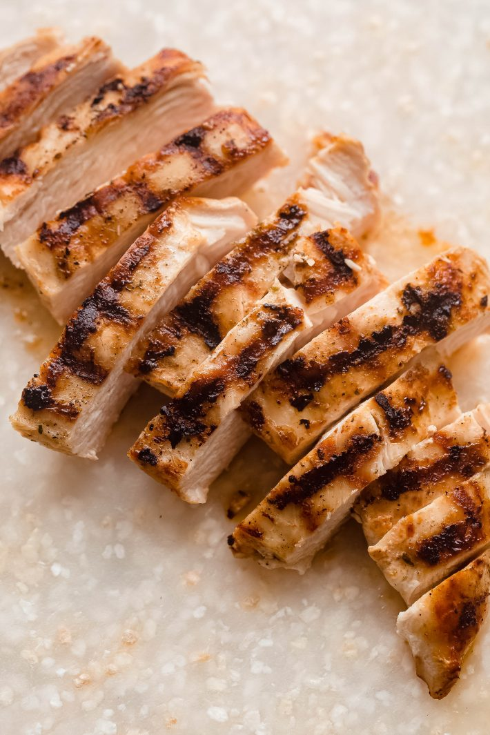 grilled chicken on speckled white cutting board