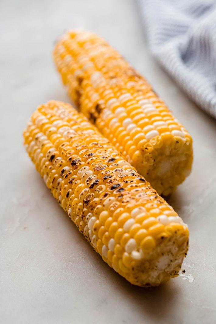 charred corn on white marble