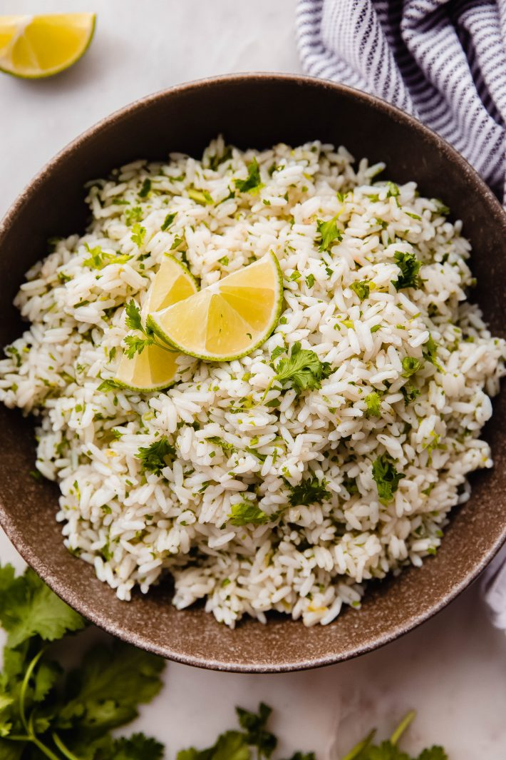 rice with cilantro and lime in olive bowl with lime wedges
