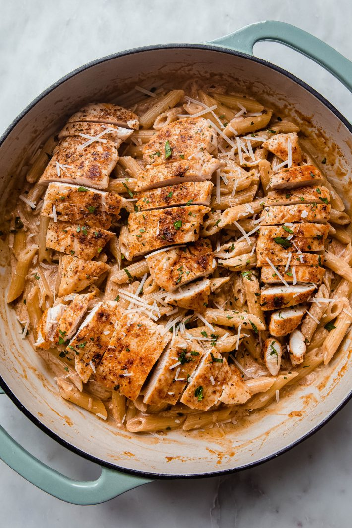 paprika chicken pasta in cast iron pan topped with parmesan cheese