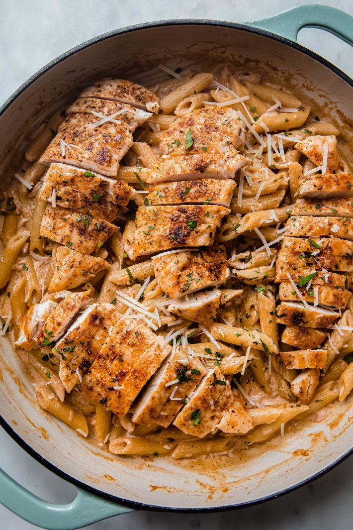 sliced chicken breasts on top of creamy pasta