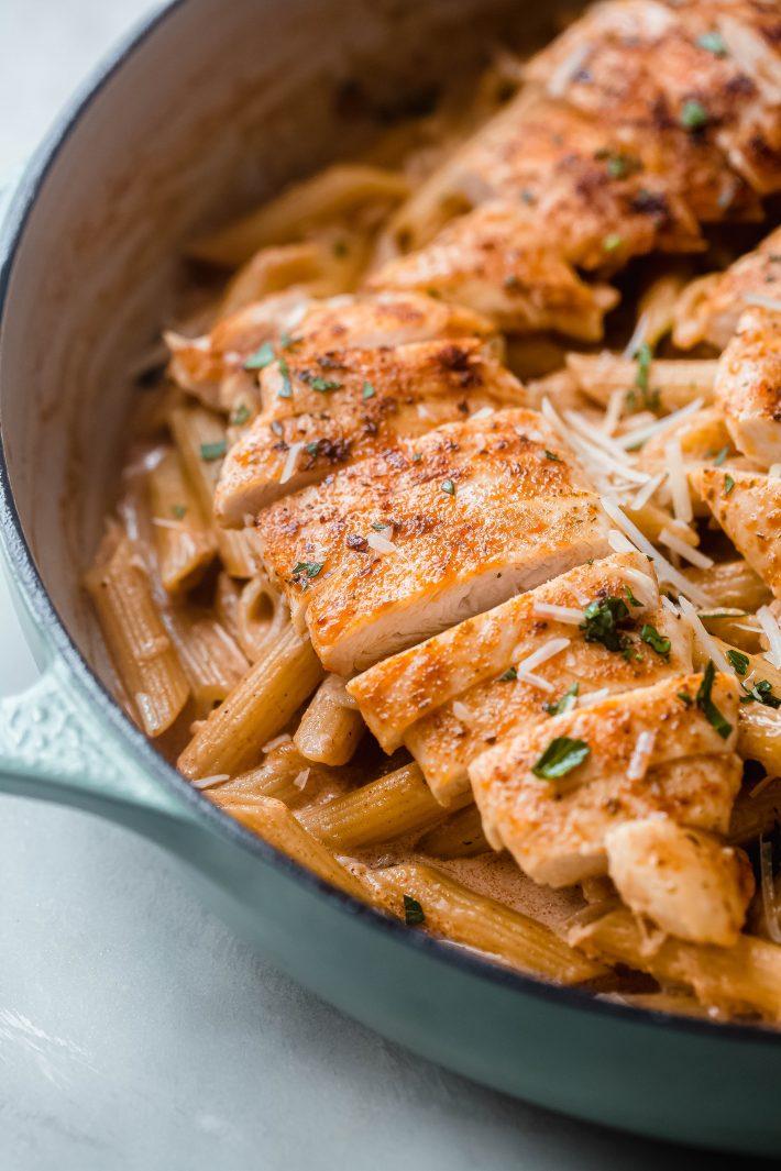 sliced chicken over paprika pasta