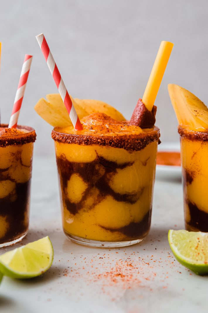 layered mangonada with lime wedges on white marble