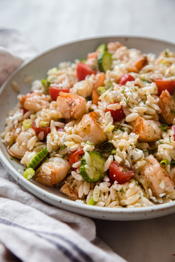 speckled plate with mediterranean shrimp salad with orzo on white marble