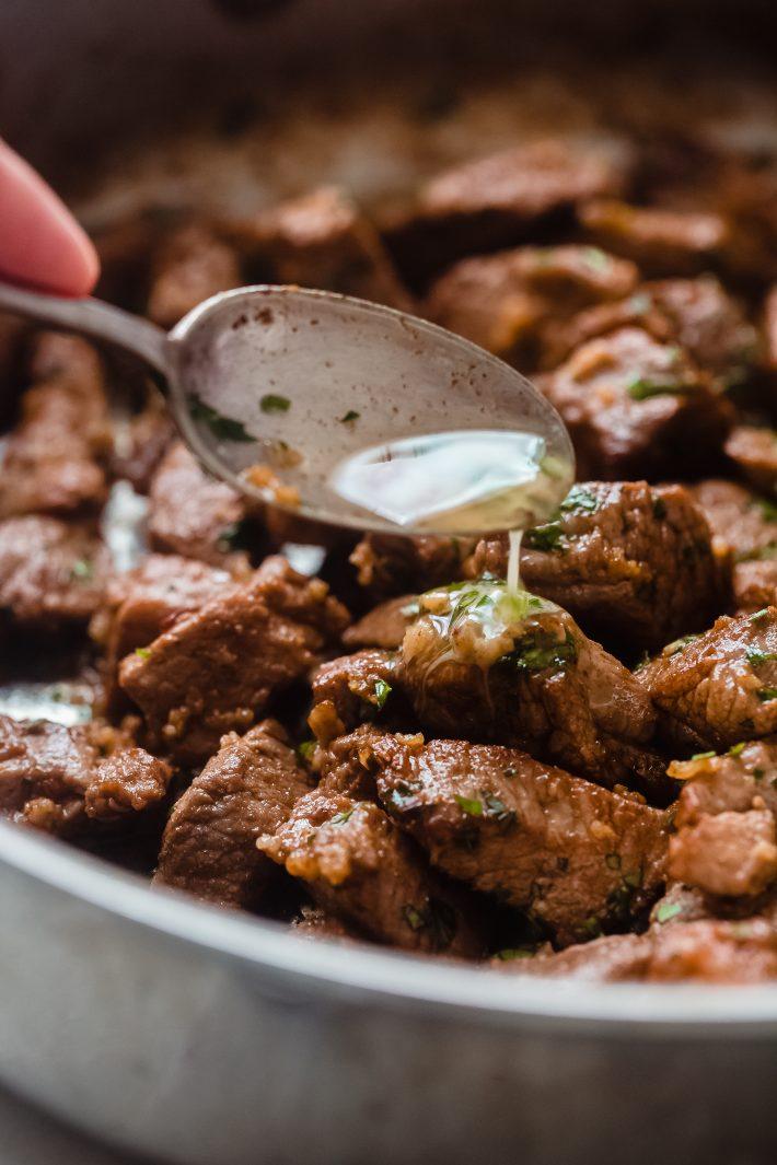 garlic butter being poured over steak bites