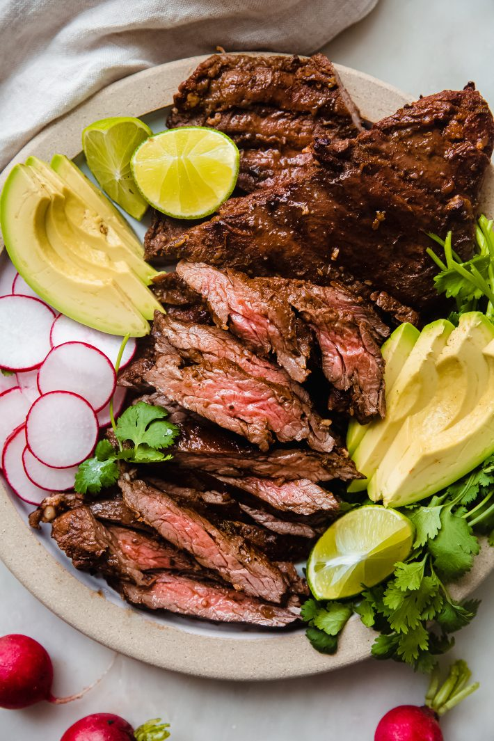 plate with sliced carne asada and fresh veggies